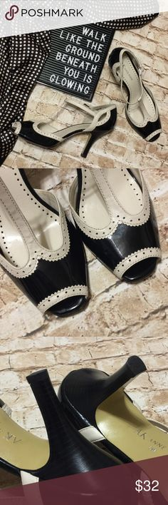 """Anne Klein Wingtip T-Strap Retro Heels Cute retro saddle-shoe look by Anne Klein. Black and cream wingtips with a t-strap buckle and a 3.5"""" heel. Pair with a retro style dress or with jeans and a turtleneck sweater. Super comfortable and easy to walk in. Excellent condition, the only flaw is on one of the t-straps there is a small yellowed spot, I believe to be a dot of the glue from the factory. As you can see in the last photo, It blends in well with the cream color and is not noticeable…"""