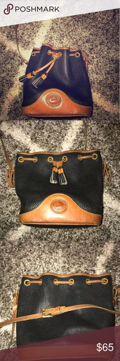 Dooney & Bourke Vintage Bucket Bag Beautiful vintage bag by Dooney & Bourke. The exterior of the bag is navy pebbled leather. The Crossbody strap and bottom of the bag are a gorgeous patina. All wear is show in photos. Ask if you have questions :) Dooney & Bourke Bags Crossbody Bags