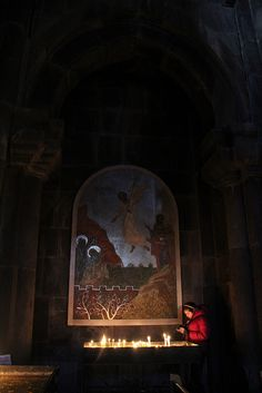 Lighting candles in a church, Armenia