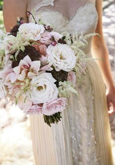 A lush bouquet of dahlias, roses, ranunculus, peonies, and crocosmia pods was offset with feathery astilbe and dramatic dark pink sedum, befitting of fall.