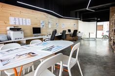 Chiralt Arquitectos I Oficina con mobiliario minimalista y revestimiento de madera en paredes.