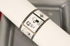 Simplement enroulées, les serviettes blanches sont maintenues à l'aide de ronds de serviettes en carton... sur le thème du cinéma bien-sûr !