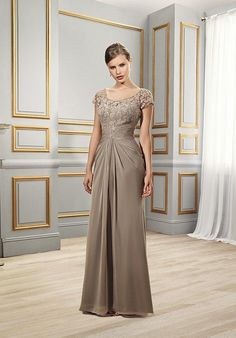 Look sophisticated in this floor length chiffon gown, specially designed for the mother of the groom at a vintage inspired garden wedding.  The short sleeved bodice is embellished with lace appliques and crystals for a truly enchanting effect.  Featuring a flattering scoop neck and an inverted basque waist.  The trumpet silhouette is perfect for curvy moms who want to groove on the dance floor.