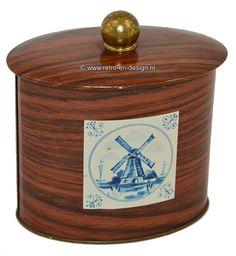 Ovaalvormig blik. Houtstructuur / houtlook  met Delftsblauwe tegel Ovaalvormige oud blikje met hout look. Ronde goudkleurige knop op het deksel. Aan voor en achterkant een delftsblauw tegeltje. Op de één een molen en op de andere een rijtje van drie gevels. zie: http://www.retro-en-design.nl/a-43599770/blikken/ovaalvormig-blik-houtstructuur-houtlook-met-delftsblauwe-tegel/