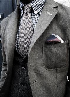 グレーのジャケットに同系色グレーのベストを合わせた着こなし、ネクタイとシャツもグレー、白、黒でまとめている統一感あふれるコーデ。