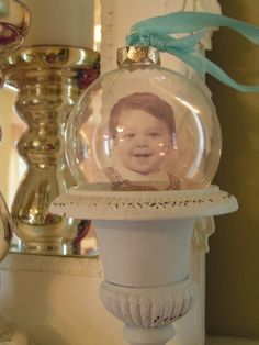 I printed his picture onto transparency paper, cut it into a circular shape, rolled it up, and slid it inside a plain glass bulb. I got the the idea from an article in Somerset Studio a couple of years ago. I made several of these that year and gifted friends and family with old photo keepsakes of loved ones.