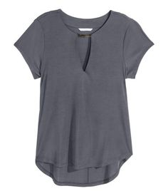 Short-sleeved top in softly draping jersey with a sheen. V-neck with metal decoration. Rounded hem, slightly longer at back.