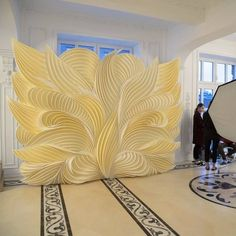 Image may contain: 1 person, indoor Stage Decorations, Paper Decorations, Wedding Decorations, Paper Flower Backdrop, Paper Flowers, Wedding Photo Walls, Photos Booth, Diy And Crafts, Paper Crafts