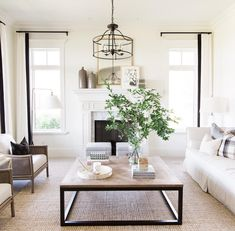 Living room with a feminine vibe. Bench sofa with 2 chairs mirroring it make it a perfect layout for conversation.   How to decorate a coffee table. Chandelier over a coffee table. Well styled living room. How to decorate a sitting room. How to arrange a front room