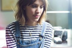 Alexa Chung style. Wearing denim dungarees with a breton and a bob hairstyle.