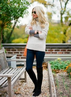 chunky cable sweater, striped shirt, skinny jeans, black knee high boots.