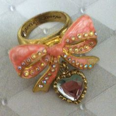 Betsey Johnson Bow Ring This beautiful light pink ring is set on gold.  The bow has ivory on the bottom of each ribbon and is edged in rhinestones.  It has a hanging clear heart charm and is engraved with betseys logo inside the ring band.  It's in great condition . . Only one tiny mark on the bottom of the ring band. Betsey Johnson Jewelry Rings