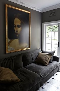 Warm gray painted living room with white crown moulding, charcoal velvet sofa and large gold-framed oil painting.