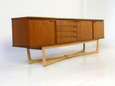 This teak sideboard was produced by Stonehill during the end of the 1960s. It features crossover legs and doors either end with the right door opening to shelving with a drop down door to the left and four drawers. It remains in a good vintage condition; one of the drawers has been repaired.