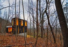 Johnsen Schmaling Architects designed the modest Stacked Cabin in a remote Wisconsin forest. Working with a tight budget, they kept the structure simple and minimized the footprint by going vertical and carving into the sloped site.