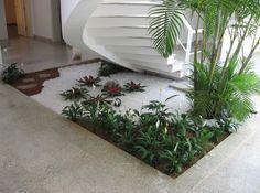 O espaço embaixo das escadas dá lugar a um charmoso jardim.