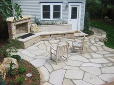 Dry-laid buff stone patio with fireplace and built-in seat wall and plantings. By Native Edge Landscapes in Boulder, Colorado.