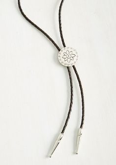 You've found your outfit's ideal finishing touch in this bolo tie from Beijo Brasil! Featuring dark brown, braided leather strands adorned with a silvery, stamped disc and molded tips, this unique accessory is the perfect example of your relaxed style! With an emphasis on the beauty of handcrafted wares, Sonoma-based brand Beijo Brasil finds inspiration in truly unique aesthetics.