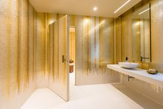 Linvisibile Brezza vertical pivot door coated with Orsoni gold mosaic