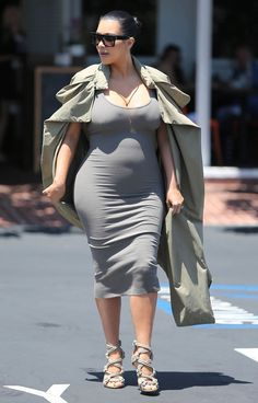 Kardashian made her rounds in Los Angeles wearing a body hugging grey dress under a khaki trench coat. For accessories she rocked designer Jimmy Choo sandals and Celine sunglasses.
