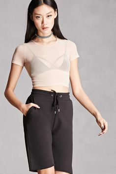 This sheer mesh knit top by Kikiriki™ features a cropped length, round neckline, and short sleeves.