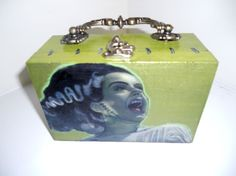 """""""Bride of Frankenstein"""" Cigar Box Purse.  Hand-painted in a lovely shade of green with stitches or staples adorning the sides of the purse so it looks as if it was stapled shut, and a Portrait of The Bride of Frankenstein on the front, complete with glow in the dark accents and a Portrait of the lovable Frankenstein on the back side."""