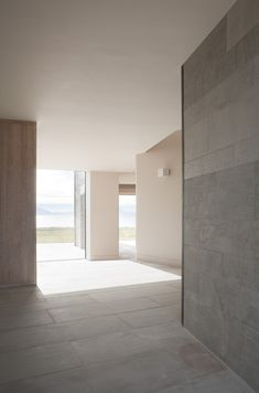 Seaside house in Ireland by Tierney Haines Architects where three sandstone wings protect an inner courtyard from coastal winds.