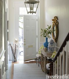 A fresh spirit starts at the front door in designer Lynn Morgan's historic Savannah row house. Family heirlooms — the gilded eagle mirror and blue-and-white pottery — mix happily with Madeline Weinrib's Celery Mu pillows, Circa Lighting's hanging lantern, and a vase from Two's Company.   - HouseBeautiful.com