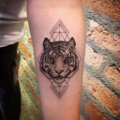 Tatuagem feita por Lucas Martinelli de São Paulo.    Rosto de tigre com linhas geométricas em volta, no antebraço.