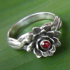 Lotus is symbol of purity. This sterling  silver open Lotus design is crowned by garnet, sparkling softly and  exuding gentle, feminine power. Perfect for every occasion.