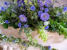 Here's an idea of a natural spray, this is on a coffin but the same idea. Where the flowers lay naturally and don't look to contrived. You could tweak this to suit your flower choices.