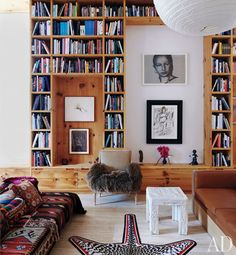 [low seating covered in tribal prints, animal rug and giant bookshelf] just my kind of space, clean yet full of comfort and personality