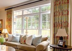 Custom drapery panels featuring contrasting edges and matching throw pillows bring style to any room. #BudgetBlinds