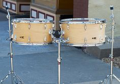 Concert Bass Toms  Tired of standing with your knee muffling an awkwardly-flattened concert bass drum in your multi-percussion set-up? These fully-adjustable Concert Bass Toms mount comfortably from tom stands, and are the perfect substitute for concert bass drums in your ensemble.  Also, these drums do a great job of rounding out a set of concert toms with their boomy low end and crispy articulation.  10x18, 10x20; plied maple; semi-gloss wax.