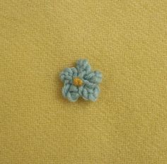 This is how I made the tiny blue flowers on my Posy Cushion . Knitted on 2 needles. Abbreviations: K = Knit St(s) = Stitch(es) tbl = throug...