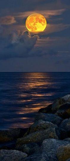 Full moon rising over Jupiter Inlet Beach in Florida .