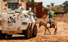A boy rides a donkey past a UN-African Union mission armoured vehicle in the war-torn town of Golo, Darfur