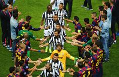 Juventus players shake hands with Barcelona players as they walk to collect their runners up medals during the UEFA Champions League Final between Juventus and FC Barcelona at Olympiastadion on June 6, 2015 in Berlin, Germany.