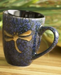 Set a bewitchingly pretty table with the cobalt-blue splendor of this classic ceramic mug. High-shine, deep speckled blue ceramic is accented with a coppery-brown dragonfly on both exterior and interior.