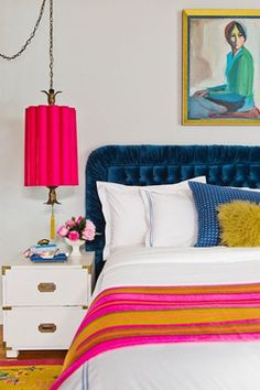 Bedroom interior in pink, yellow & blue.  Velvet headboard, pendant light, throw, cushions