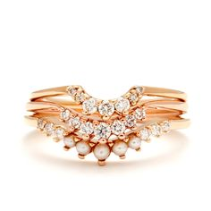 Nesting SuiteNo.09 features a tier ofour signature Tiara Bands. Featuring our newest Seed Pearl Tiara Curve Band with hand set pearls and whitediamonds. This band is nested amongst the diamond dusted Tiara and Lunabands in warmtoned yellow and rose gold. This suite and can be ordered in any combination of the gold colors.