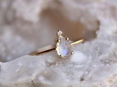 Unleash your inner unicorn! With its beautiful, swirling colors accented by the tiniest diamond, our 14K Unicorn Tears ring is just the thing! The teardrop shaped moonstone has hints of purple, blue and pink shining throughout. - Pear Moonstone measures 6mm x 4mm - Floating diamond diamond