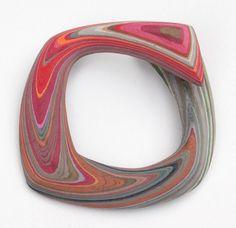 Bracelet by Susanne Holzinger.  Layers of glued and carved paper.