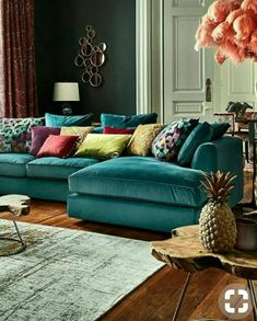 Love the teal velvet sectional couch. This has a upscale boho feel. Great use of colors. (Harrington Large Chaise Sofa)