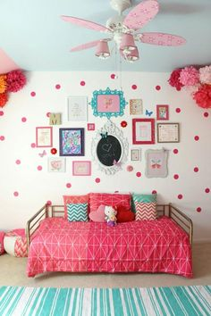 If your little girl adores all things pink, she'll love this bright pink polka dot bedroom with fun paper flower decorations.