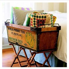 A vintage banana box propped on 2 folding wooden camp stools to hold pillows at the foot of the bed - clever!