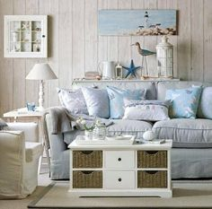Seaside living room with white-washed wall panelling, a light blue sofa piled with cushions and an armchair, a coffee table chest and side table with lamp. Coastal Living Rooms, Cottage Living, My Living Room, Living Area, Coastal Living Magazine, Beach Cottage Style, Beach Cottage Decor, Coastal Style, Coastal Cottage