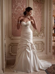 Wedding dresses come in many fabrics and styles but Casablanca Bridal 2086 wedding dress in a fit and flare satin design is the one that touches your heart. As you gaze upon the beautiful ruching of the bust and its adornment at the empire waist, you fall in love all over again with the promise of what's to come. The asymmetrical ruching over the hips is met with pickups over the thighs and the gown turns to pure beauty and indulges your sense of vision.