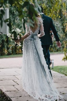 Wedding dress palest blue with flower petals appliqued all over and whole pink flowers on the train hem. Blue sash belt tied in a trailing bow