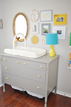 Old dresser, changing pad with mobile on top, photos on wall.